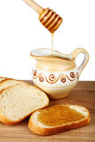 Honey in a jug and loaf on board Stock Images