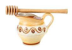 Honey in a jug and wooden stick Stock Photo