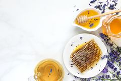 Honey with lavender tea and honeycombs with freash flowers on white marble table. healthy food. top view Royalty Free Stock Images