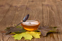 Honey and leaves on a wooden table Royalty Free Stock Photo