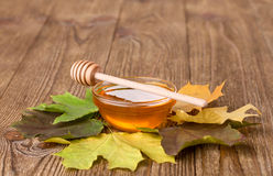 Honey and leaves on a wooden table Royalty Free Stock Photos