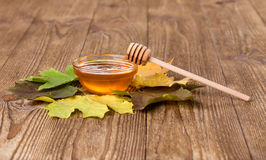 Honey and leaves on a wooden table Royalty Free Stock Photography