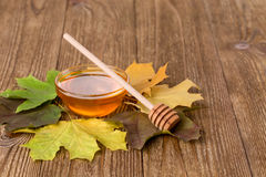 Honey and leaves on a wooden table Stock Image