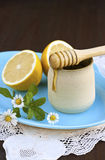 Honey and lemon. Fresh golden honey running from wooden drizzler to a ceramic jar stock image