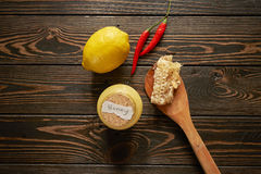 Honey with lemon and chilies. On wooden background Royalty Free Stock Image