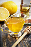 Honey, lemon and a cup of tea. On a wooden table Royalty Free Stock Photo