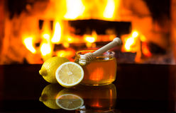 Honey and lemon in front of warm fireplace. Royalty Free Stock Photography