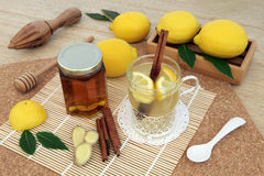Honey Lemon and Ginger Spice Drink. Hot lemon, honey and ginger drink for cold remedy in a glass tea cup with cinnamon stick spice and fresh fruit on bamboo over Stock Photo