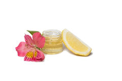 Honey and lemon isolated. Honey in bottle, pink alstromeria and lemon isolated Royalty Free Stock Photography