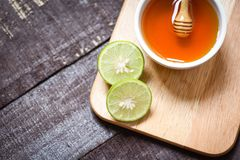 Honey lemon lime on cutting board with honey cup on dark wooden background. Honey lemon lime on cutting board with honey in cup on dark wooden background royalty free stock images