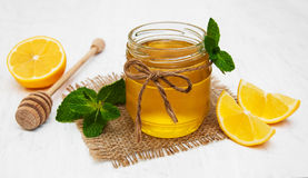 Honey with lemon and mint. On a old white wooden background Royalty Free Stock Photos