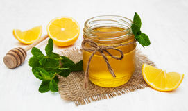 Honey with lemon and mint. On a old white wooden background Royalty Free Stock Image
