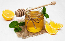 Honey with lemon and mint. On a old white wooden background Royalty Free Stock Photo