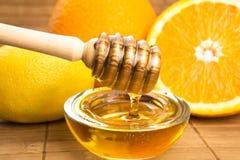 Honey with lemon and orange fruits Stock Photography