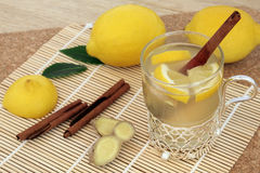 Honey Lemon and Spice Drink. Honey, lemon, cinnamon and ginger spice drink for cold and flu relief with silver and glass mug with fresh fruit on   a bamboo mat Stock Image