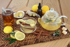 Honey Lemon and Spice Drink. Honey, lemon, ginger and cinnamon drink for cold and flu relief with glass tea cup and pot, herbs, spices, medicine bottle, cough Stock Photo