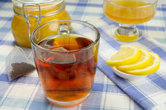 Honey, lemon, tea. Cup of tea with a jar of honey and lemon slices on the table. Pyramid tea bag nearby Royalty Free Stock Photography