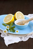 Honey and lemons. Fresh golden honey, juicy lemons and chamomile - natural cold and flu remedies royalty free stock photos
