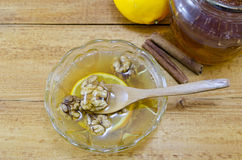 Honey, lemons, cinnamon and walnuts on a table Royalty Free Stock Images