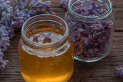 Honey and lilac flowers in glass jars on wooden background Royalty Free Stock Photo