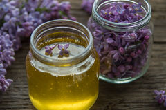 Honey and lilac flowers in glass jars on wooden background Stock Image