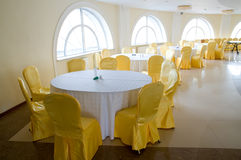 Honey and milk interior. Restaurant white tables and golden yellow chairs stock photos