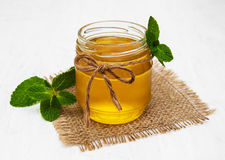 Honey with mint. Honey with  mint on a old white wooden background Royalty Free Stock Photos