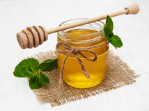 Honey with mint. Honey with  mint on a old white wooden background Royalty Free Stock Images