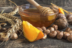 Honey, nuts, wheat and orange fruit on an old vintage wooden table Royalty Free Stock Photos