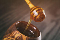 Honey in olive wood pot with dipper on table Royalty Free Stock Photos