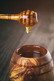 Honey in olive wood pot with dipper on table Stock Photography