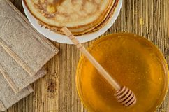 Honey pancakes and bread on the weathered wooden surface. On an old wooden board honey pancakes and bread Royalty Free Stock Photo