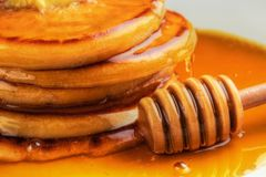 Honey with pancakes Stock Photography