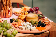 Honey with pear and cheese. Honey with pear, cheese, grapes and olives decorate the festive table Stock Photo