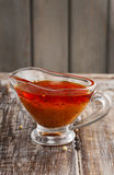 Honey and pepper red marinade in glass gravy boat Stock Images