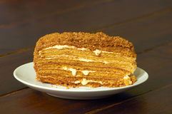 Honey piece of cake. Honey layered piece of cake on white plate on wooden table royalty free stock photos