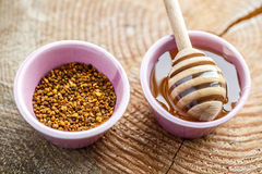 Honey pollen and honey with wooden stick Royalty Free Stock Image