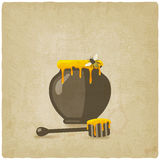 Honey pot with bee and wooden dipper on old Stock Image