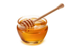 Honey pot and dipper isolated on white Royalty Free Stock Photo