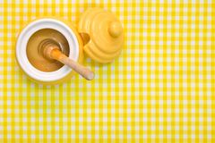 Honey pot and dipper on yellow background with copy space. stock image