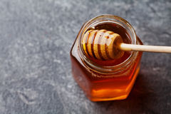 Honey in a pot or jar on black kitchen table from above Royalty Free Stock Photos
