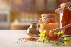 Honey pots honeycomb and bee pollen on white kitchen table. Composition with honey pots, honeycomb and bee pollen on white kitchen table with flowers. Front view royalty free stock image