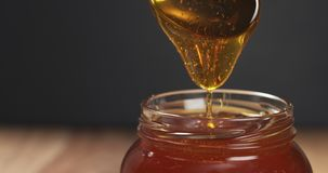 Honey pour with spoon in glass jar. Wide photo Stock Photos