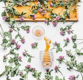 Honey poured from glass jar with dipper, honeycomb frame and wild flowers on white background, top view Royalty Free Stock Image