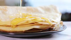 Honey is poured on a stack of pancakes. Slow motion. stock footage