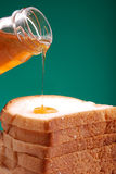Honey pouring. Sweet honey pouring on bread stock photo