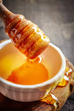 Honey pouring into bowl Stock Photography
