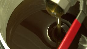 Honey Pouring Into Bucket. Handheld, aerial, close up shot of honey pouring out of a nozzle and into a bucket stock video footage
