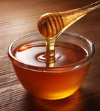Honey pouring from drizzler into the bowl. Bowl is on a wooden table stock photo