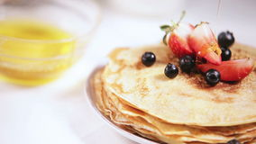 Honey pouring on the fresh cooked pancakes with blueberries and strawberries stock video footage